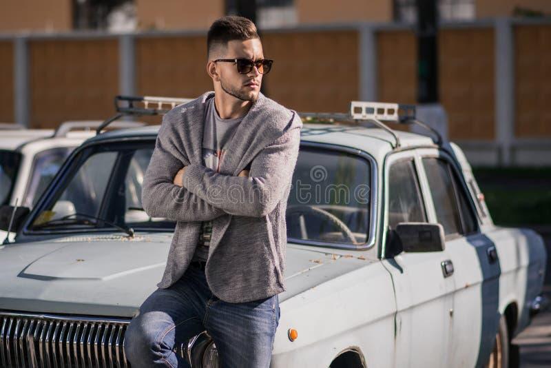 Modieuze en modieuze mens rond oude auto stock foto