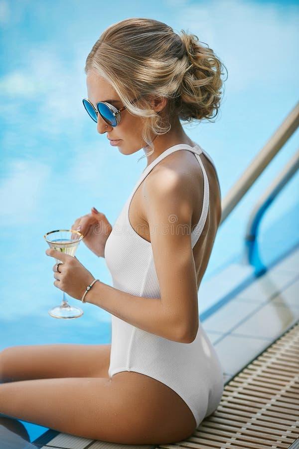 Modieuze en mooie jonge modelblondevrouw met sexy lichaam in modieus wit zwempak en zonnebril, met glas stock foto's