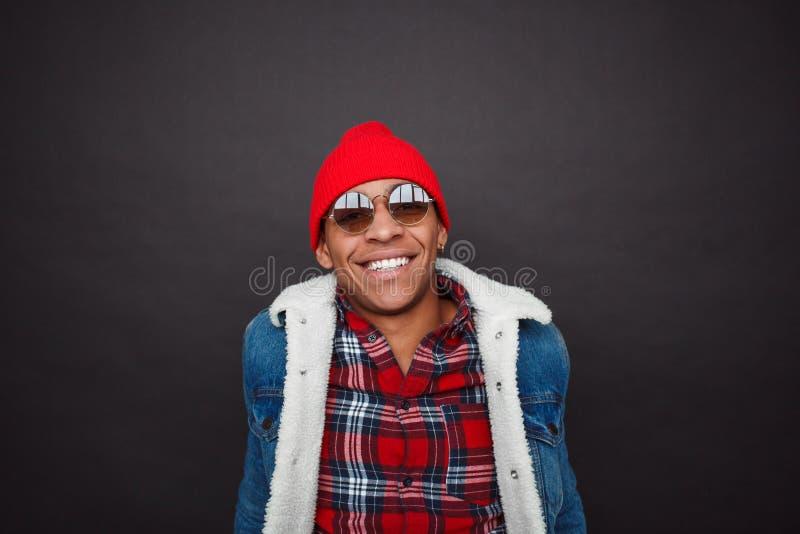 Modieuze etnische mens die op zwarte glimlachen stock afbeelding