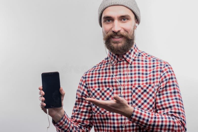 Modieuze gebaarde blauw-eyed mens die zijn slimme telefoon en oortelefoons houden stock foto