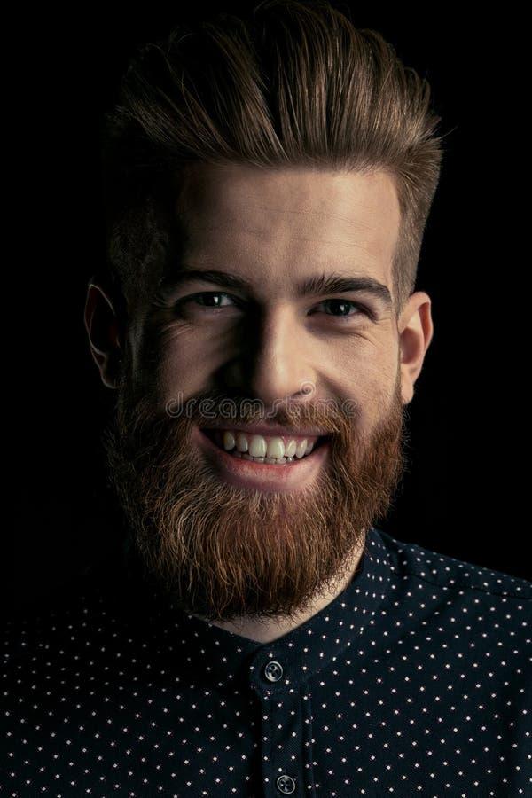 Modieuze gebaarde mens die hipster bij camera glimlachen royalty-vrije stock foto's