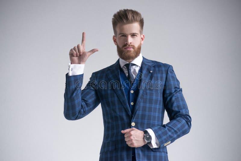 Modieuze gebaarde zakenman die met hand op jasje met vinger op grijs benadrukken royalty-vrije stock afbeelding