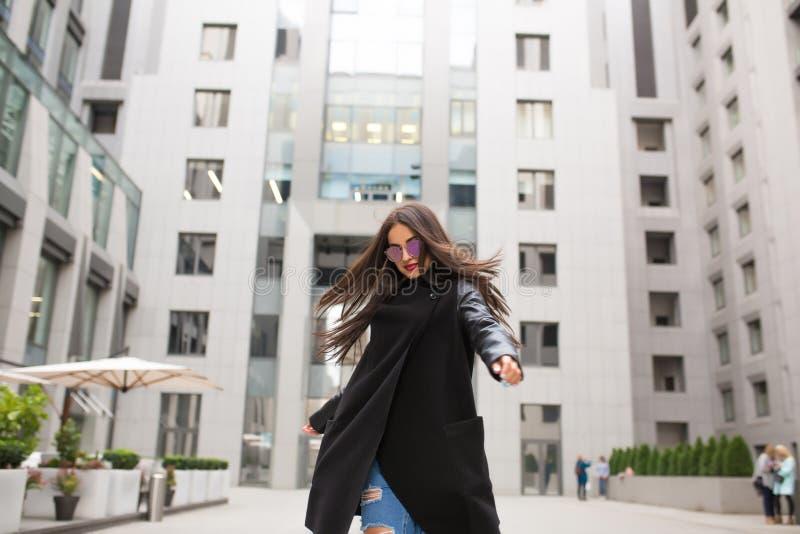Modieuze geklede donkerbruine vrouw met haar die in de wind blazen wal royalty-vrije stock afbeeldingen