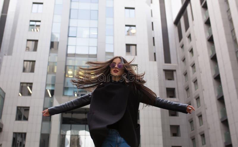 Modieuze geklede donkerbruine vrouw met haar die in de wind blazen wal stock afbeeldingen