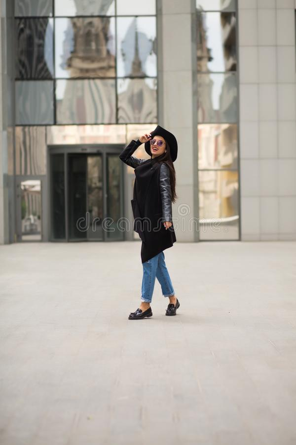 Modieuze geklede jonge vrouw die dichtbij de stadswandelgalerij lopen royalty-vrije stock afbeeldingen