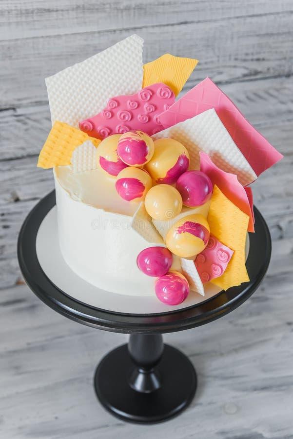Modieuze gekleurde cake die op zwart dienblad op de witte houten achtergrond blijven De vieringsgift van de verjaardagspartij royalty-vrije stock afbeeldingen