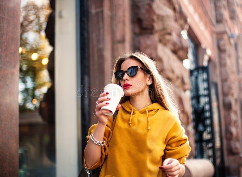 Modieuze gelukkige jonge vrouw die boyfrend jeans, wit tennisschoenen helder geel sweatshirt dragen Zij houdt koffie om te gaan p stock afbeeldingen