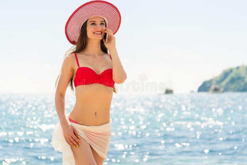 Modieuze geschikte jonge vrouw die op mobiele telefoon op het strand spreken royalty-vrije stock foto's