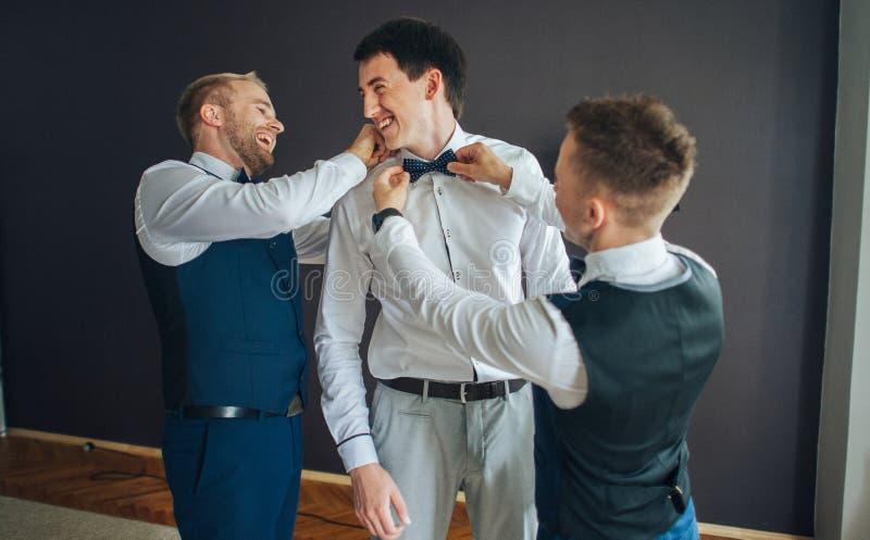 Modieuze groomsmen die gelukkige bruidegom helpen die klaar in morni worden stock afbeelding