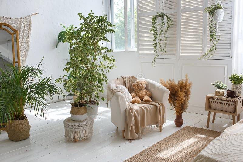 Modieuze heldere zolder comfortabele woonkamer met leunstoel, groene installaties, jaloezie, witte bakstenen muren en houten vloe royalty-vrije stock afbeelding