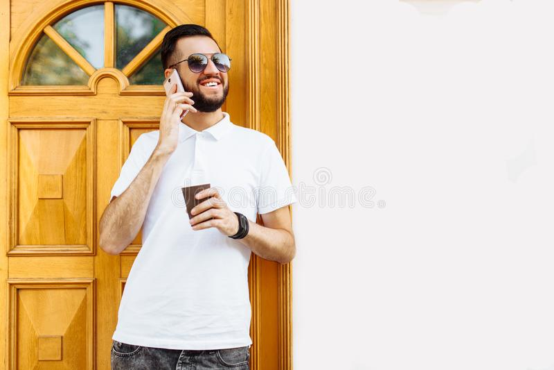Modieuze hipster in een wit overhemd en zonnebril, op backgrou stock foto