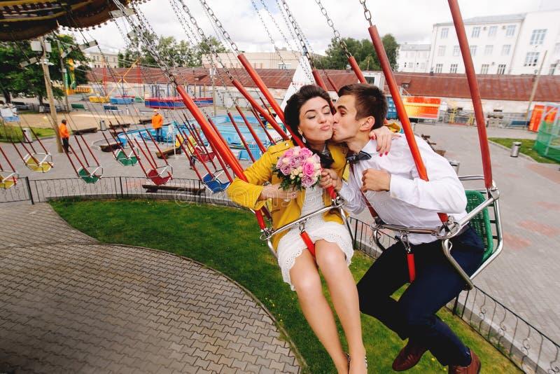 Modieuze hipsterjonggehuwden die terwijl het berijden op hoge carrousel in pretpark kussen Expressief huwelijkspaar in Carnaval stock foto's