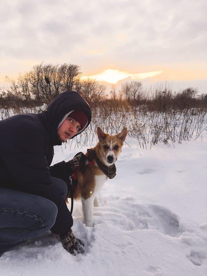 Modieuze hipstermens die met leuke gouden hond in sneeuw koud park lopen Mensenzitting met zijn hond in de winter wit bos in warm royalty-vrije stock afbeeldingen