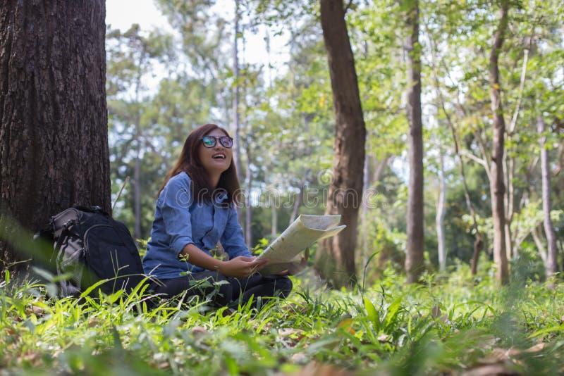 Modieuze hipsterreiziger die kaart bij zonnig bos en meer in het bergenlandschap onderzoeken royalty-vrije stock fotografie