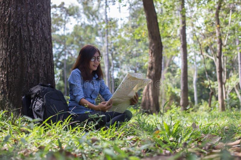 Modieuze hipsterreiziger die kaart bij zonnig bos en meer in het bergenlandschap onderzoeken royalty-vrije stock foto's