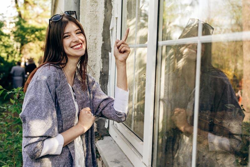 Modieuze hipstervrouw die en op serrevenster glimlachen richten royalty-vrije stock foto