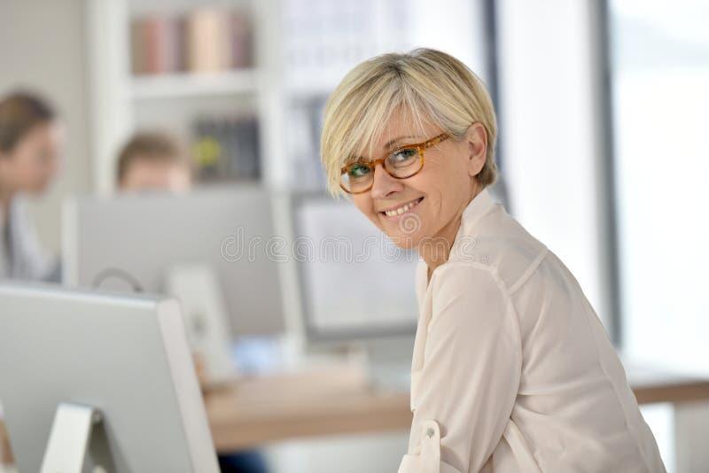 Modieuze hogere vrouw die op kantoor werken stock afbeelding