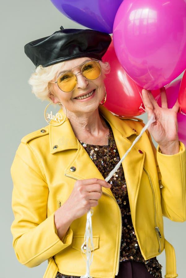 modieuze hogere vrouw in geel jasje met kleurrijke ballons, stock afbeelding