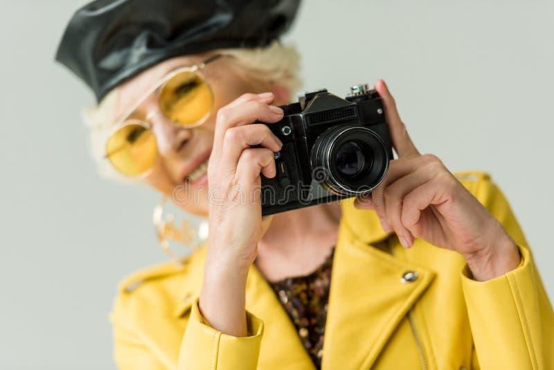 modieuze hogere vrouw in gele jasje en leerbaret die foto op camera nemen, stock afbeeldingen