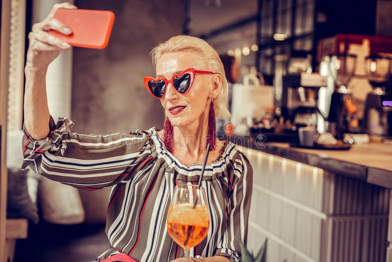 Modieuze hogere vrouw in hart gevormde zonnebril die rode smartphone dragen stock fotografie