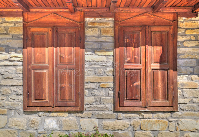 Modieuze houten vensters op steenmuur stock afbeeldingen