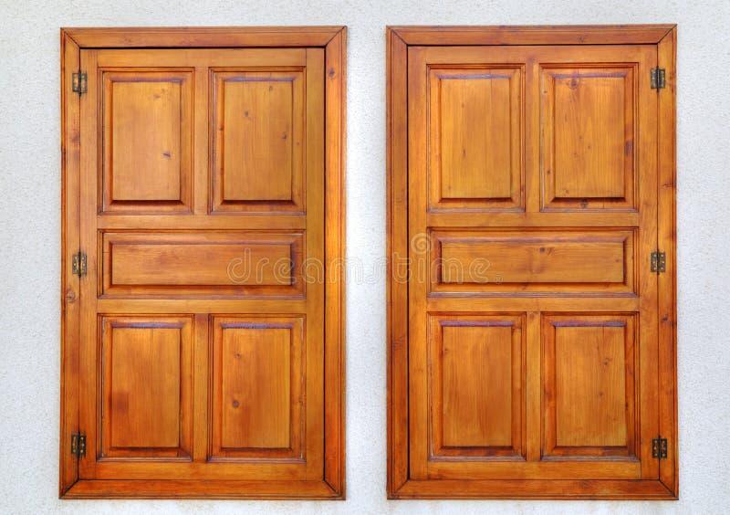 Modieuze houten vensters op steenmuur stock foto's