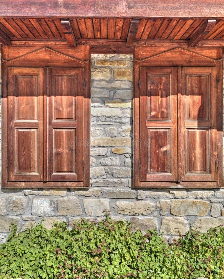 Modieuze houten vensters op steenmuur royalty-vrije stock afbeeldingen