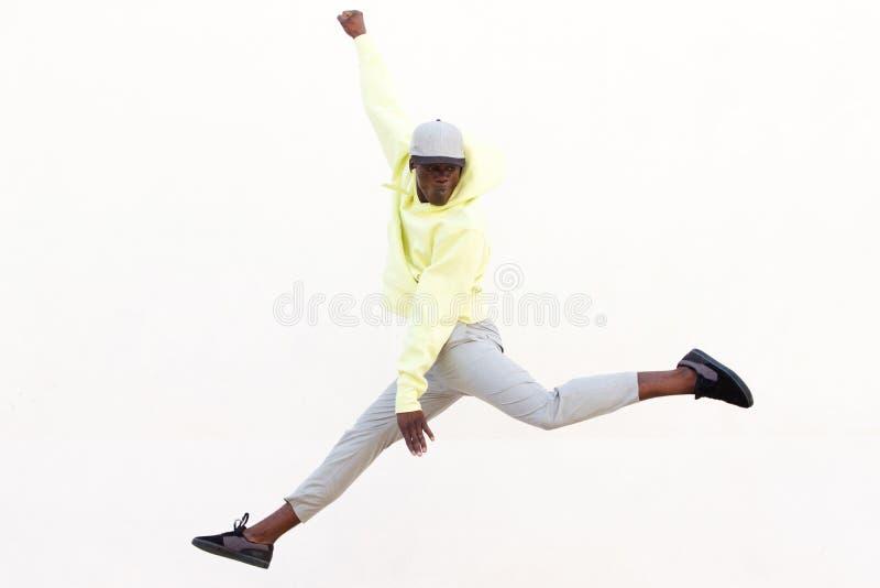 Modieuze jonge Afrikaanse Amerikaanse mens die en op witte achtergrond springen dansen royalty-vrije stock afbeelding