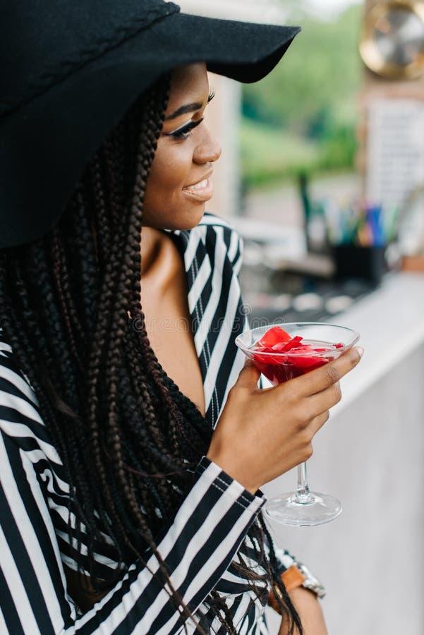 Modieuze jonge Afrikaanse vrouw met charmante glimlach die haar cocktail isenjoying terwijl opzij het kijken De gelukkige jonge z stock foto