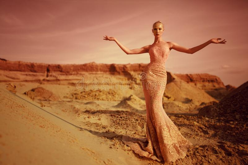 Modieuze jonge blondevrouw in de woestijn in lange gouden kledingstribune met open handen, tijdens bij zonsondergangachtergrond stock afbeelding