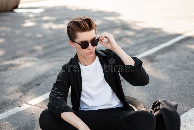 Modieuze jonge hipstermens in in zonnebril in een elegant overhemd in gestreepte broek die op een zonnige dag in openlucht rusten royalty-vrije stock foto's