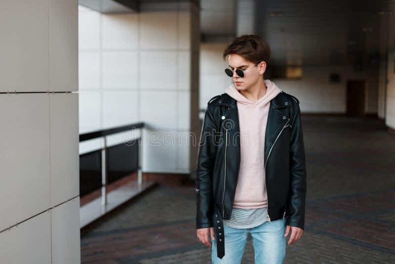 Modieuze jonge hipstermens in zwarte zonnebril in modieus zwart jasje in roze sweatshirt in in jeans in een grijze t-shirt stock afbeeldingen