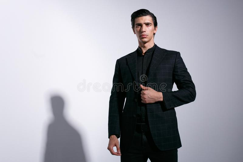 Modieuze jonge knappe mens in een modieus kostuum, dat hand op controleursjasje houdt, dat op witte achtergrond wordt geïsoleerd stock fotografie