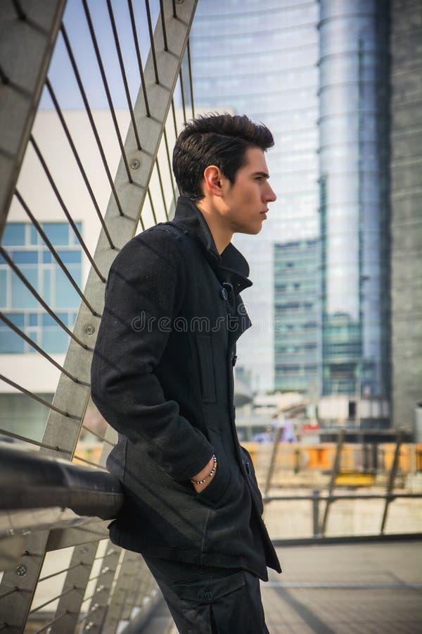 Modieuze Jonge Knappe Mens in Zwarte Laag die zich in de Straat van het Stadscentrum bevinden stock afbeelding