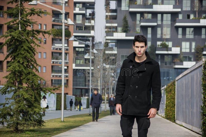 Modieuze Jonge Knappe Mens in Zwarte Laag die zich in Stad bevinden royalty-vrije stock fotografie