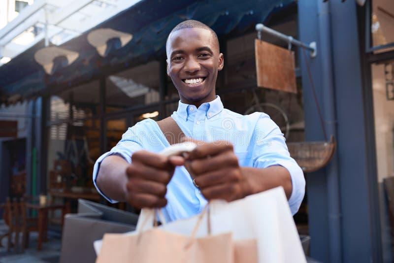 Modieuze jonge mens die zich buiten het steunen van het winkelen zakken bevinden royalty-vrije stock afbeelding