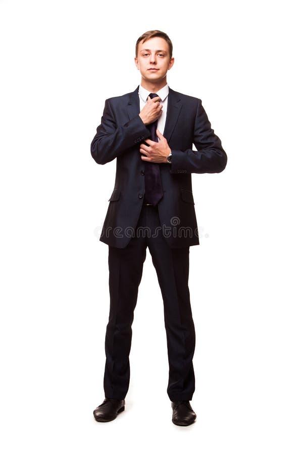 Modieuze jonge mens in kostuum en band Bedrijfs stijl De knappe mens bevindt zich, bekijkt de camera en bevestigt zijn band royalty-vrije stock foto's