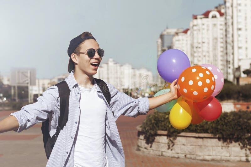 Modieuze jonge mens met ballons op de stadsstraat stock fotografie