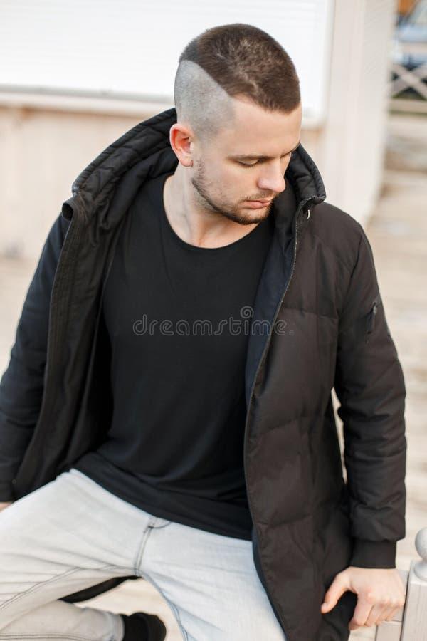 Modieuze jonge mens met een kapsel in de modieuze winter royalty-vrije stock afbeelding