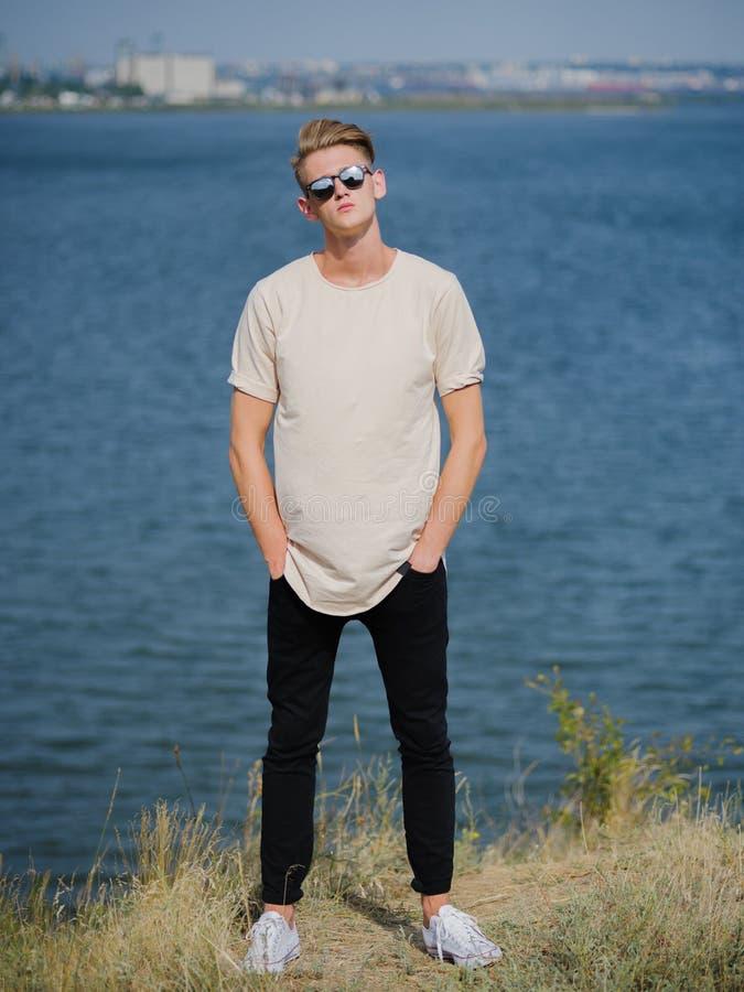 Modieuze jonge mens in zonnebril Lange, koele kerel die dichtbij de rivier op een vage achtergrond lopen Het concept van de unive stock fotografie