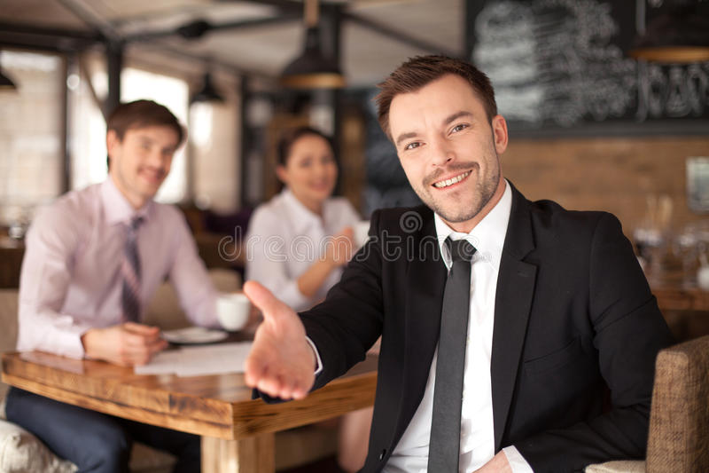 Modieuze jonge mensenzitting in restaurant stock afbeelding