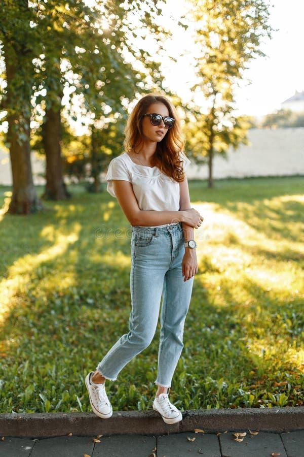 Modieuze jonge roodharige hipster vrouw in uitstekende jeans in een witte T-shirt in in zonnebril in modieuze tennisschoenen die  royalty-vrije stock foto's