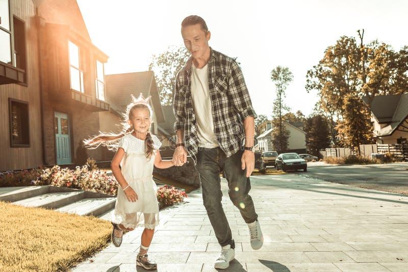 Modieuze jonge vader in geruit overhemd en jeans die met meisje spelen stock foto