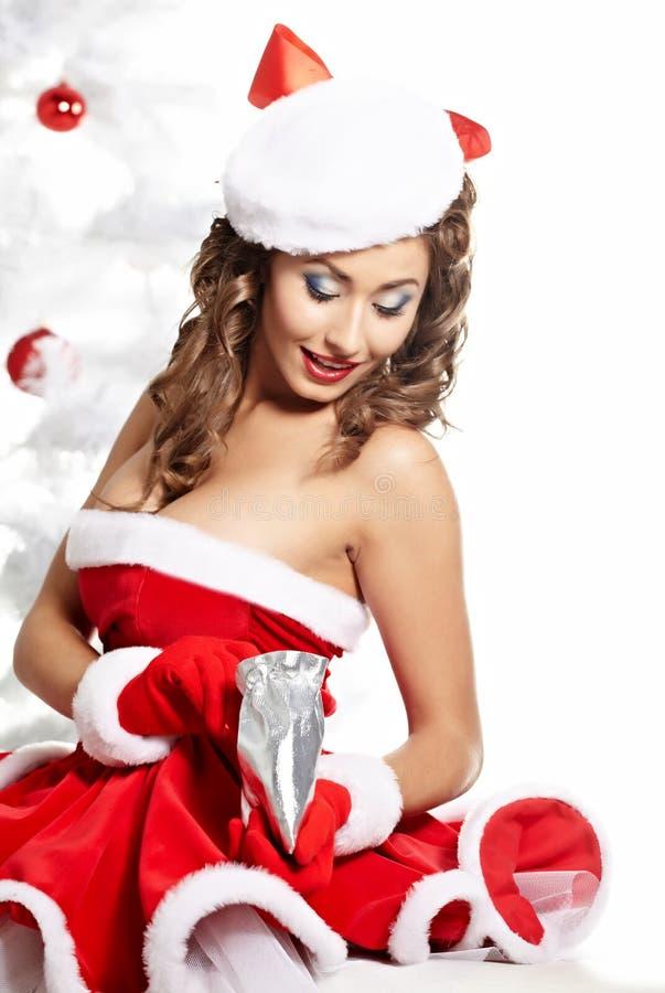 Modieuze jonge vrouw in de kleren van de Kerstman stock fotografie