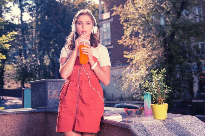 Modieuze jonge vrouw die één of andere koude de zomercocktail op warme dag nippen royalty-vrije stock foto's
