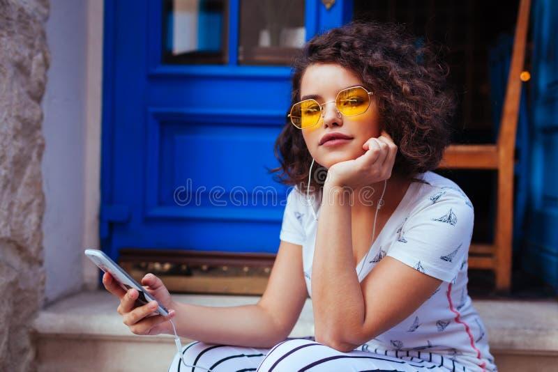Modieuze jonge vrouw die aan de muziek luisteren die smartphone gebruiken Openluchtportret van modieus meisje die glazen dragen royalty-vrije stock afbeeldingen
