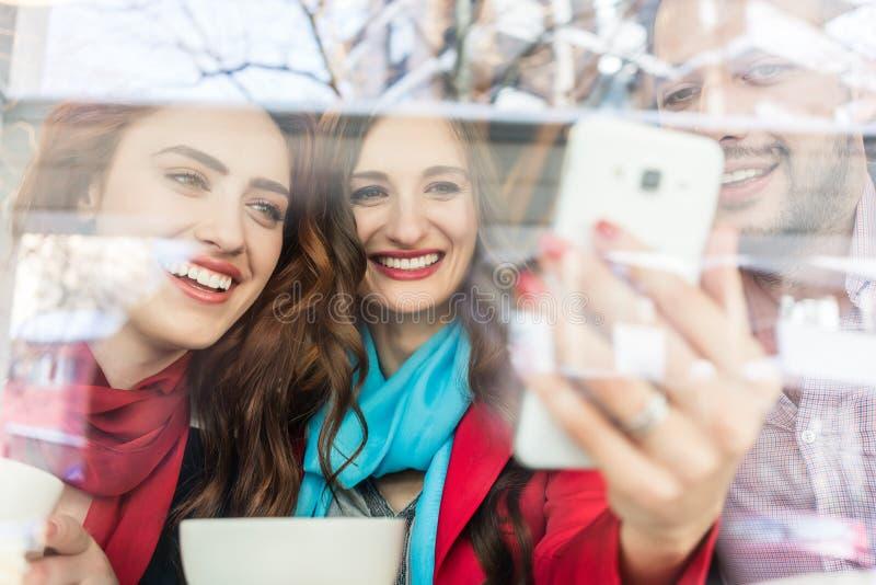 Modieuze jonge vrouw die aan haar beste vriendenbeelden tonen op mobiel stock afbeeldingen
