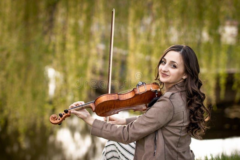 Modieuze jonge vrouw die de viool in het park spelen stock afbeelding