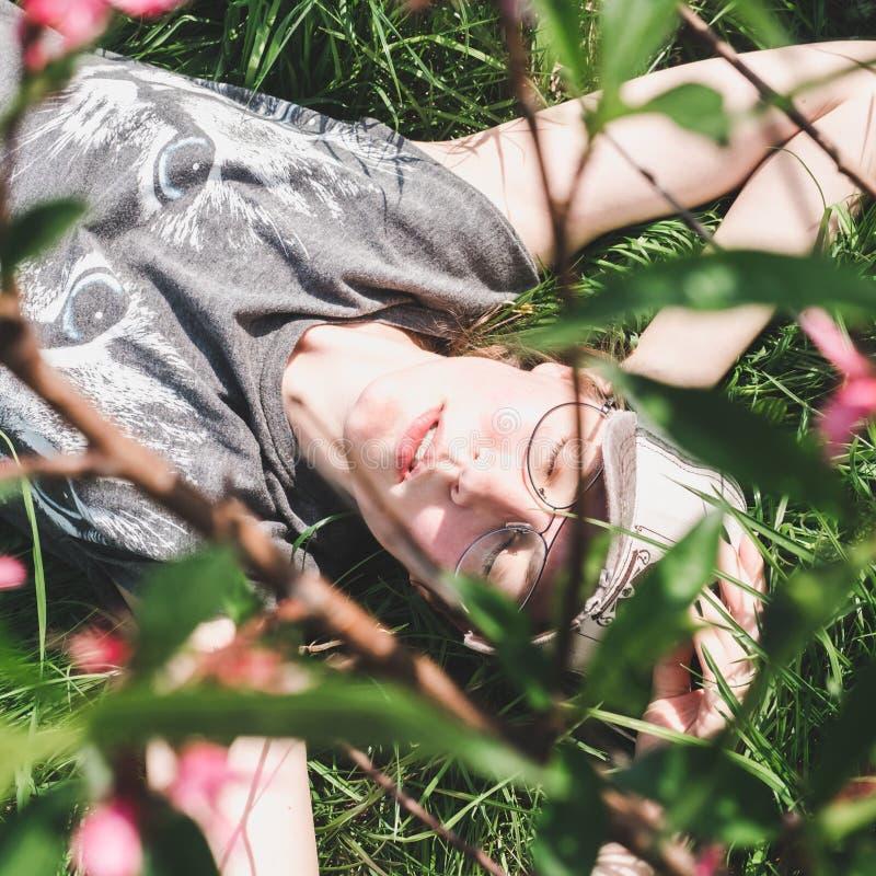 Modieuze, jonge vrouw die, dreamily op het gras liggen royalty-vrije stock afbeelding