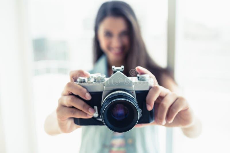 Modieuze jonge vrouw die een foto nemen bij camera royalty-vrije stock afbeelding